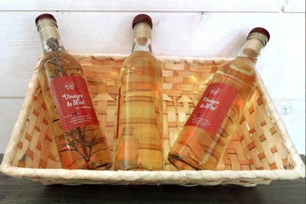 bouteilles de vinaigres de miel dans une corbeille