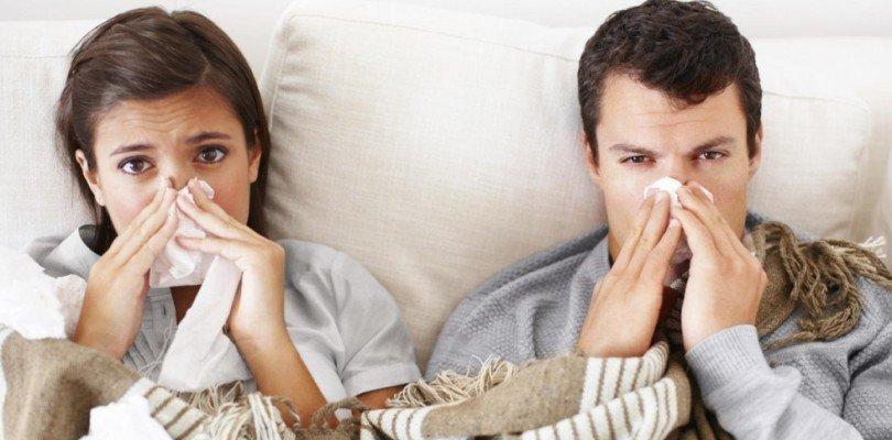 Photo d'un couple enrhumé pour illustrer les effets bénéfiques de la gelée royale sur la toux et les maladies hivernales.