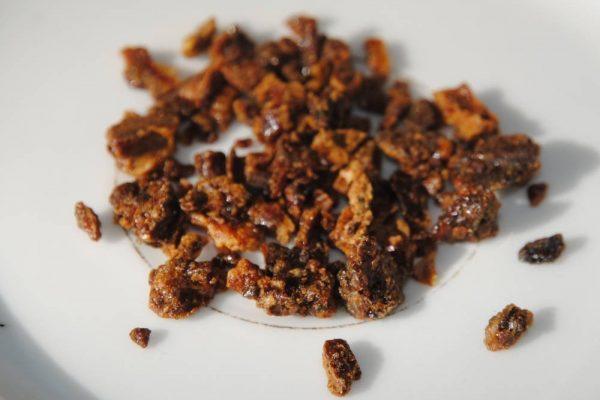 Photo de la propolis brute (pâte séchée brune).