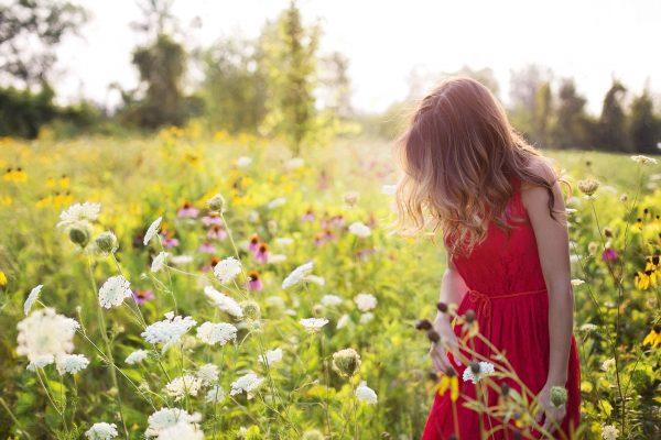 Les bienfaits du pollen de l'abeille : femme dans un pré fleuri.