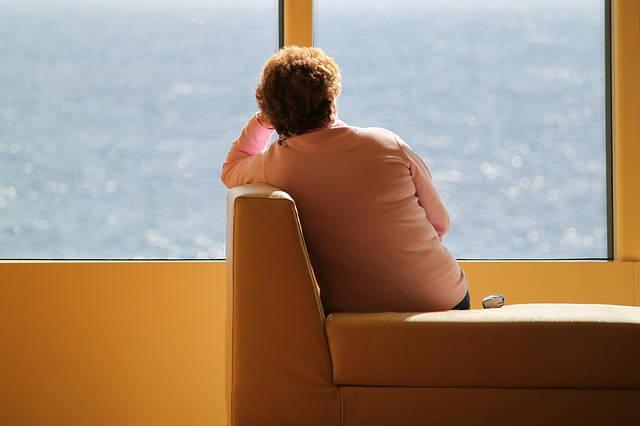 Photo d'une femme assise de dos, elle regarde par une baie vitrée la mer, elle semble mélancolique. La gelée royale peut être bénéfique dans le traitement de la dépression.