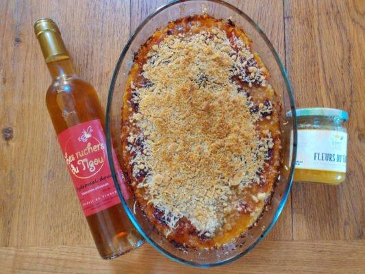 Photo du crumble salé chèvre, miel et tomates cuit avec un pot de miel et une bouteille d'hydromel.
