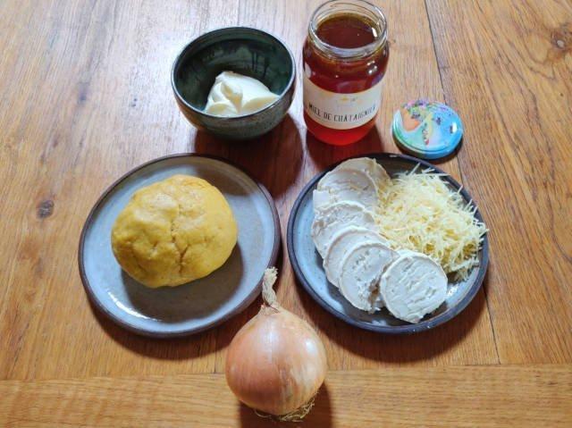 Ingrédients pour faire la tarte : oignon, pâte brisée, chèvre, fromage râpé, miel, crème fraîche.