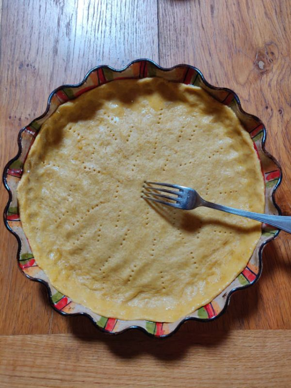 Pâte brisée étalée dans un joli plat à tarte en céramique.