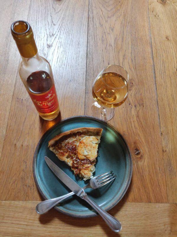 Assiette avec une part de tarte aux oignons, chèvre et miel accompagnée d'un verre d'hydromel.