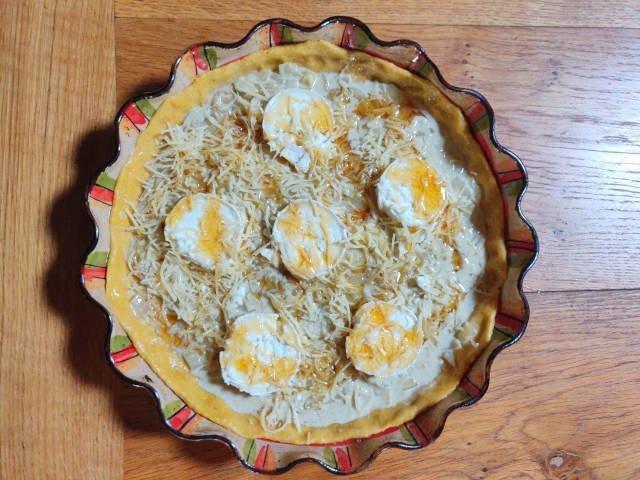 Tarte prête à cuire : préparation avec les rondelles de chèvre, le râpé et le miel déposé en ruban.