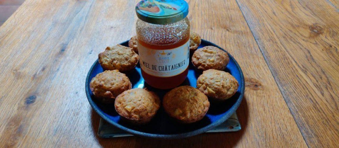 Muffins au miel et aux pommes dans une assiette avec un pot de miel de châtaignier.